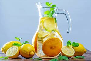 Glass of lemonade with ice cubes and mint leaves on wooden background