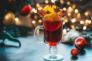 Glass of mulled wine on a beautiful Christmas background with Christmas tree and bokeh (Flip 2019)
