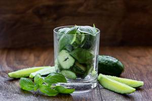 Glass with cucumber slices and Basil leaves - ingredients for green smoothie