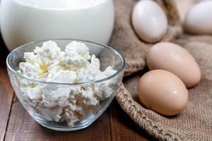 Glasschüssel mit frischem Hüttenkäse, Karaffe mit Milch und braunen Eiern auf Jutesack