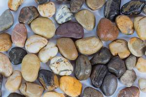Glatte Flusssteine verschiedener Formen und Farben als Hintergrund