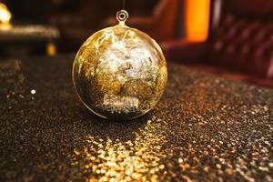 Glitzernde goldene Kugel zur Dekoration mit Lichtern auf einem Tisch