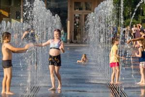 Glückliche Kinder spielen in einem Springbrunnen in Moskau
