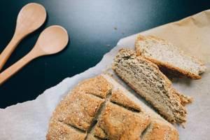 Glutenfreies Brot auf Backpapier mit Kochbesteck aus Holz