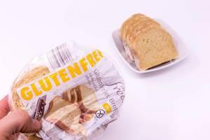 Glutenfreies Brot - in Verpackung mit Scheiben im Hintergrund