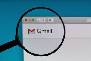 Gmail Logo und Schriftzug, vergrößert durch ein Lupenglas dargestellt