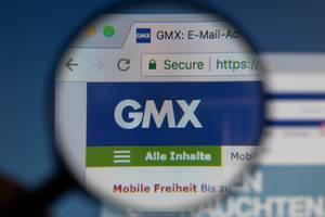GMX-Logo am PC-Monitor, durch eine Lupe fotografiert