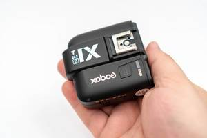 Godox X1 flash controller in the hand above white background (Flip 2020)