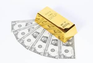 Gold bar with hundred dollar bills