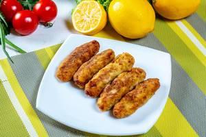 Goldbraun gebratene Fischstäbchen auf weißem Teller dekoriert mit Zitronen und Tomaten