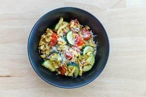 Goldbraun gebratene Spätzle mit getrockneten Tomaten und Zucchini. Draufsicht