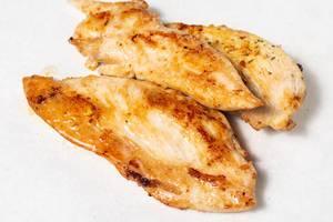 Goldbraun gegrilltes Fleisch vom Hähnchen freigestellt vor weißem Hintergrund