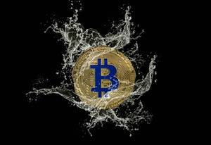 Golden Bitcoin and water splash on dark background