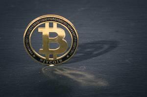 Golden Bitcoin on black background