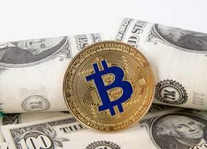 Golden Bitcoin with dollar banknotes