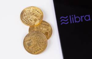 Golden coins next to smartphone with Libra cryptocurrency logo