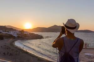 Golden hour - man takes mobile phone photo of the sunset at the coast of the Greek island Paros