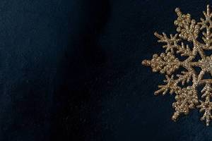 Golden snowflake on black background with free space (Flip 2019)