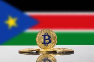 Goldene Bitcoin-Münze steht vor der Flagge des neu gegründeten Staates Südsudan