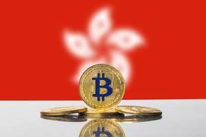 Goldene Bitcoin-Münze vor der weißen Blüte auf der Flagge der Sonderverwaltungszone Hongkong