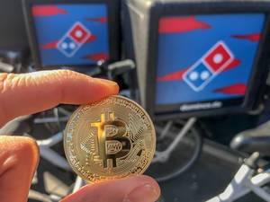 Goldene Bitcoin-Münze zwischen zwei Fingern, vor den Dominos Lieferservice-Fahrräder in der Kölner Neustadt