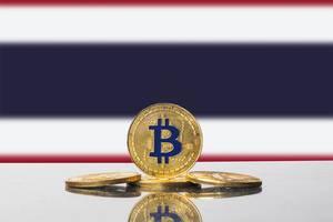Goldene Bitcoin-Münzen vor der Flagge des südostasiatischen Königreichs Thailand