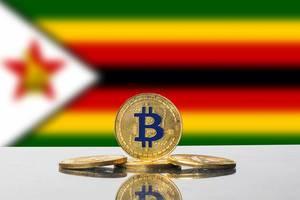 Goldene Bitcoins auf spiegelnder Oberfläche vor der Flagge von Simbabwe