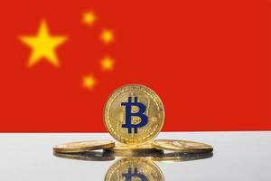 Goldene Bitcoins, eine Kryptowährung, mit Flagge der Volksrepublik China im Hintergrund