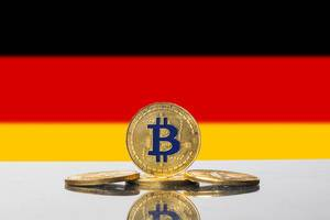 Goldene Bitcoins vor der Flagge der Bundesrepublik Deutschland, auch Schwarz-Rot-Gold genannt