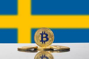 Goldene Kryptowährungs-Münze von Bitcoin vor dem gelben Kreuz der Flagge von Schweden