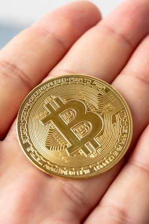 Goldene Metal-Bitcoinmünze liegt auf der flachen Hand