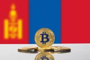 Goldene Münze der Kryptowährung Bitcoin mit der Flagge der Mongolei im Hintergrund