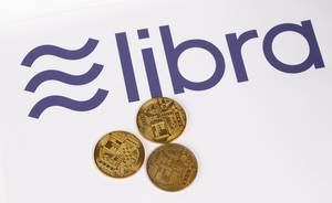 Goldene Münzen mit Libra Kryptowährung als Logo im Hintergrund