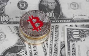 Goldene und silberne Bitcoin Münzen auf hundert Dollar Banknoten