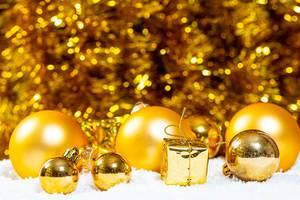 Goldene Weihnachtsbaumkugeln im Schnee vor goldenem Hintergrund