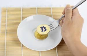 Goldener Bitcoin auf einer Gabel