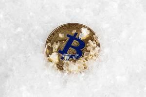 Goldener Bitcoin im Schnee steht für Eiszeit der Kyptowährungen