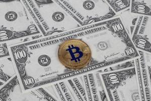 Goldener Bitcoin liegt auf verteilten US-Dollar Noten
