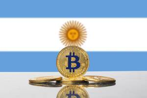 Goldener Bitcoin steht unter der Sonne auf der im Hintergrund sichtbaren Flagge von Argentinien