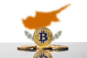 Goldener Bitcoin steht vor kupferfarbenen Umrissen Zyperns auf dessen Flagge im Hintergrund