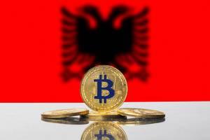 Goldener Bitcoin vor dem schwarzen, zweiköpfigen Adler der Flagge Albaniens im Hintergrund