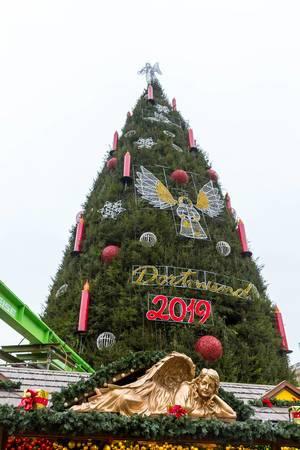 Goldener Engel vor dem großen, geschmückten Weihnachtsbaum auf dem Weihnachtsmarkt in Dortmund 2019