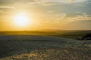 Goldener Sonnenuntergang über Vietnam, betrachtet von den weißen Sanddünen in Mui Ne