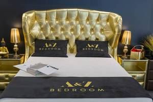 Goldenes Bett neben goldenen Lampen und Tischen und einer Buddhafigur in luxuriösem Hotelzimmer