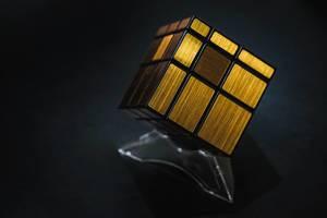 Goldenes Würfelpuzzle auf einem Plastikständer vor weißem Hintergrund