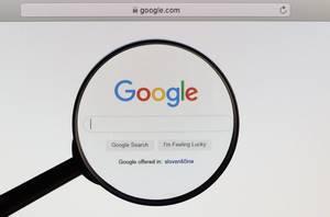 Google Logo und Suchzeile, vergrößert dargestellt durch ein Lupenglas