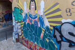 Graffiti eines lächelnden Mannes an Hauswand