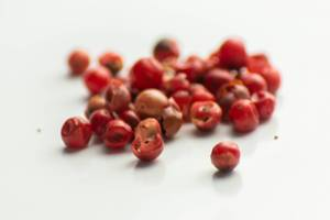 Grains of red pepper scattered on a white background