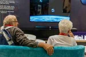 Grandparents rest on the couch during the high-tech exhibition IFA in Germany, with 75 8K Mini LED television in the background