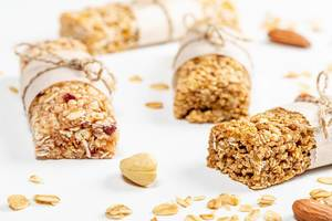 Granola bars with oat flakes, dried fruits and seeds on a white background